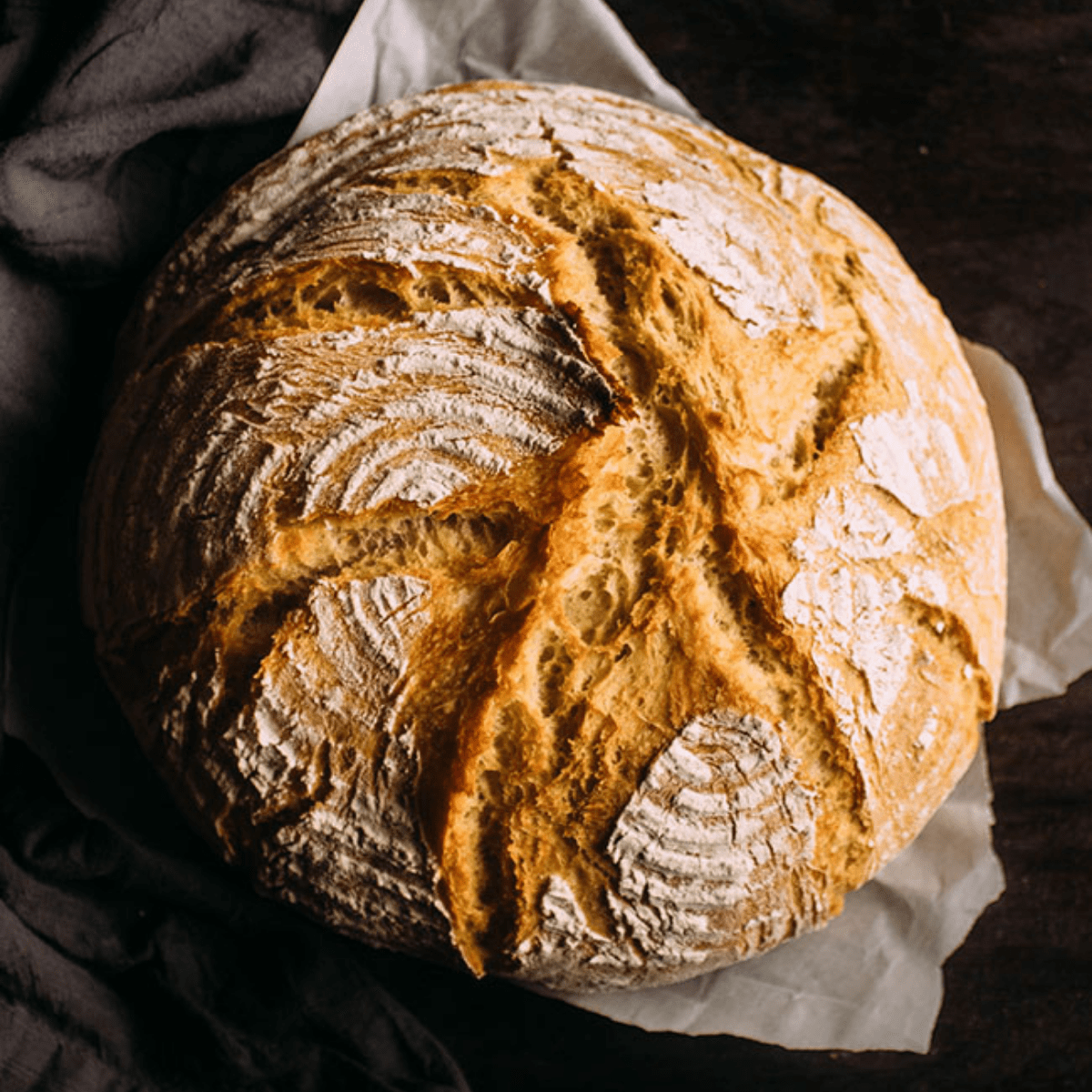 A loaf of homemade french bread on a dark background.
