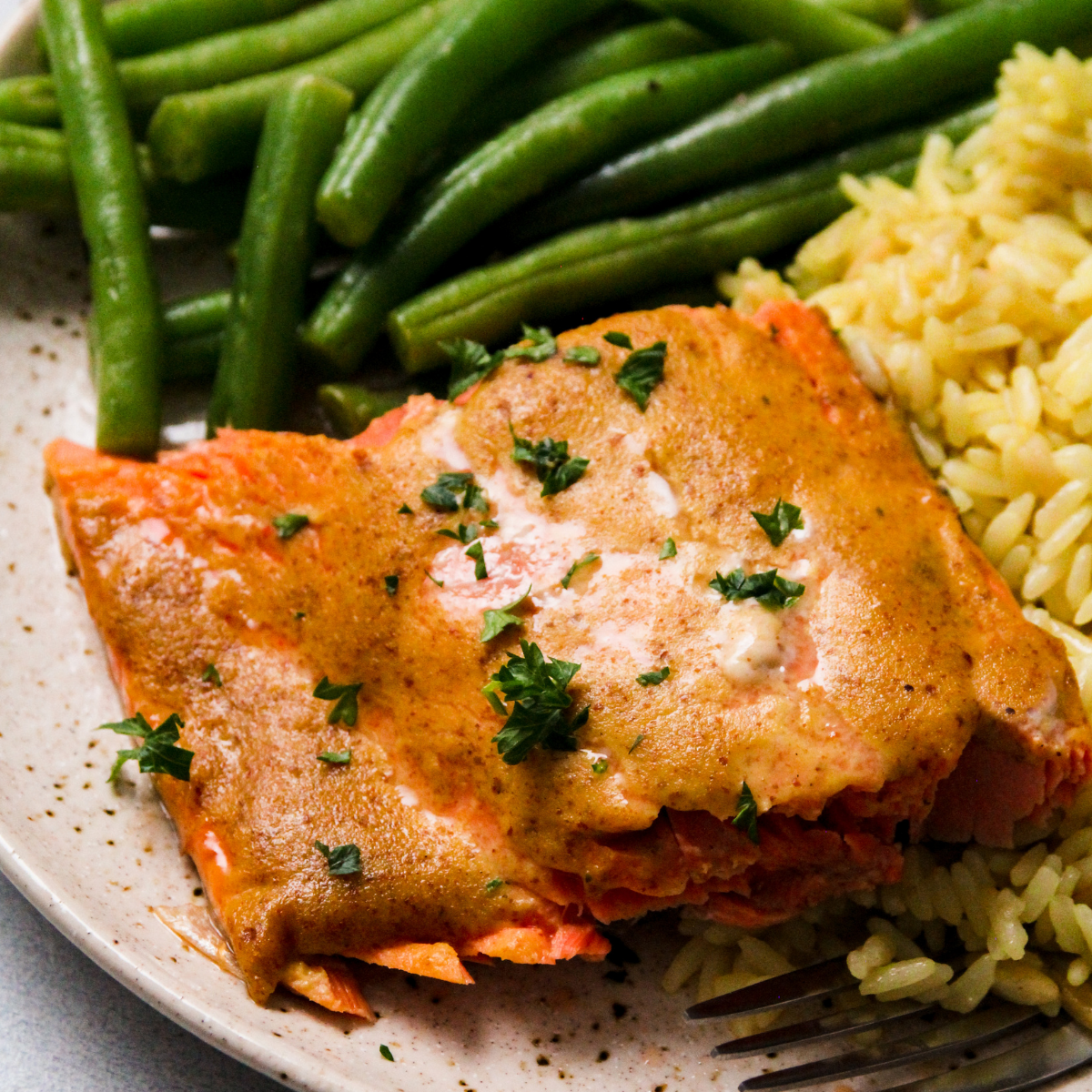 Salmon with mustard sauce and parsley on a tan plate.