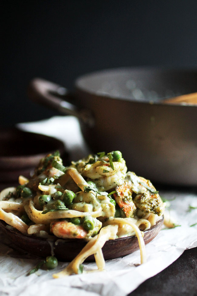 Shrimp fettuccine on a wooden plate topped with fresh peas and chopped basil