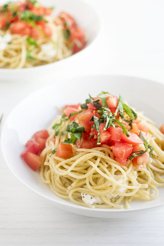 Caprese pasta in a shallow white bowl with fresh basil and tomatoes.