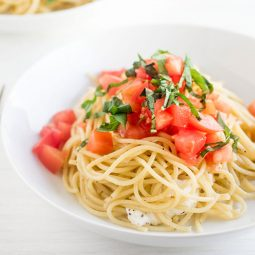 Spaghetti in a shallow white bowl topped with chopped tomatoes and sliced basil.