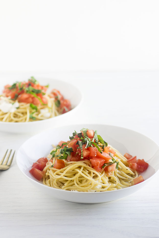 white bowl filled with spaghetti noodles and topped with chicken, diced tomatoes, and chopped basil