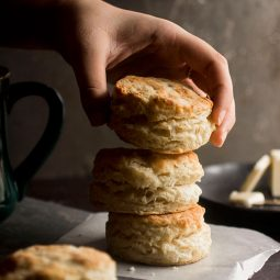 Woman's hand adding a gruyere biscuit to a stack of biscuits.