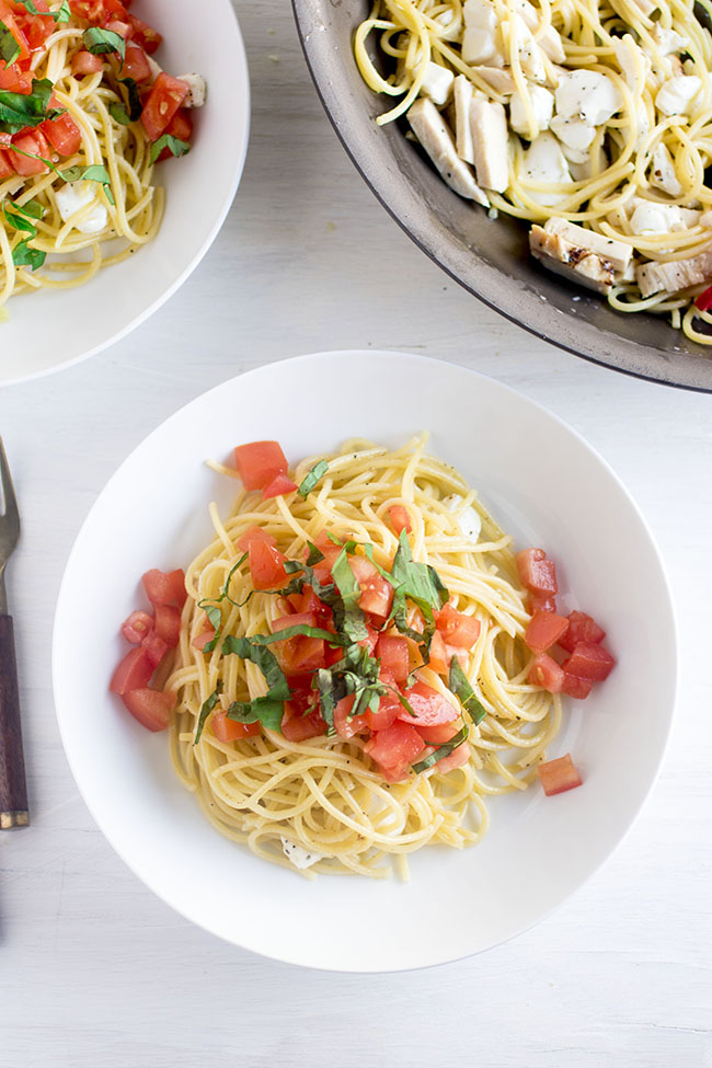 Overhead photo of spaghetti topped with tomatoes and basil in a white bowl on a white background
