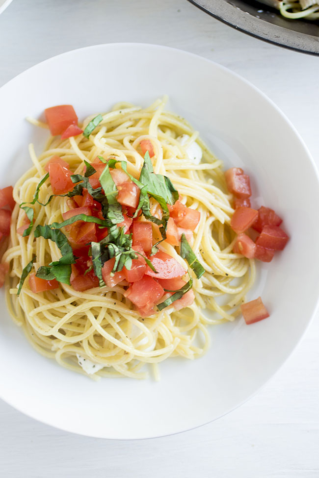 Caprese spaghetti in a white bowl with tomatoes and basil.
