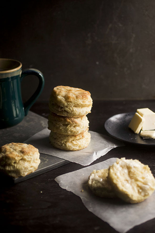 stack of three biscuits surrounded by single biscuits and a plate of butter on a black background
