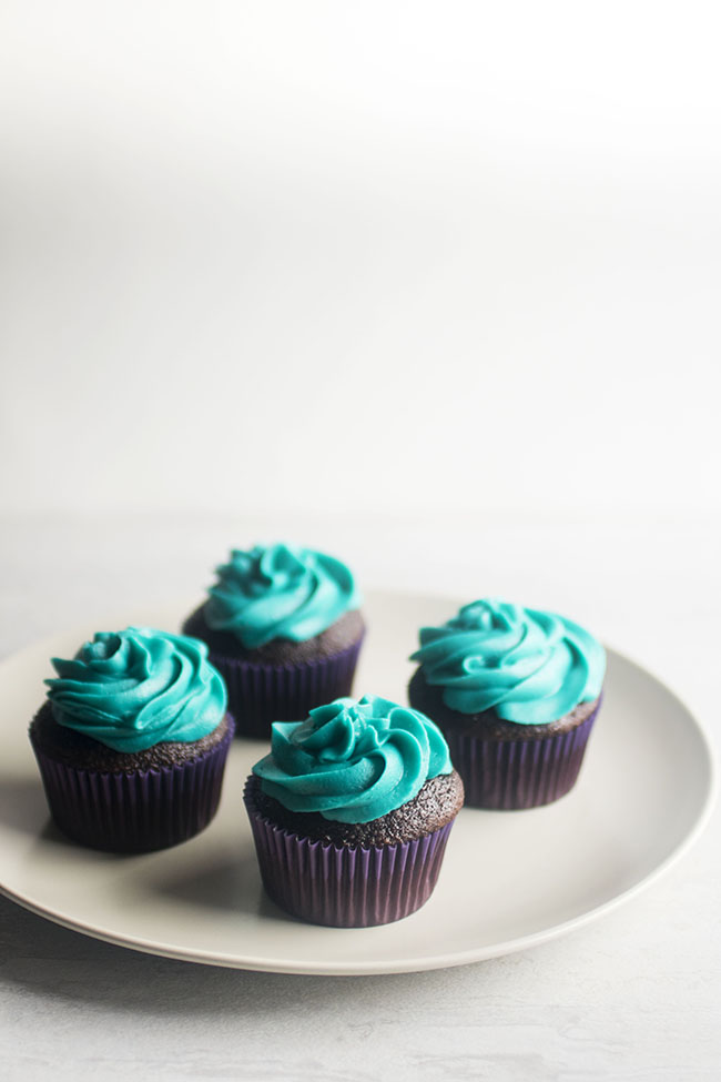 Four cupcakes with blue frosting on a white plate.
