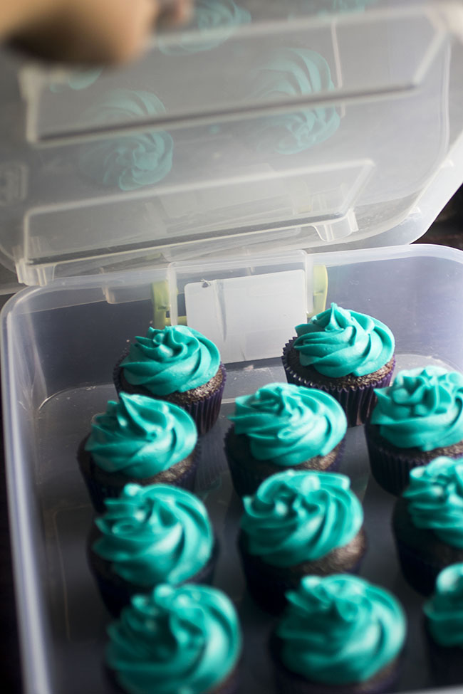 Closing the lid of a storage bin filled with cupcakes.