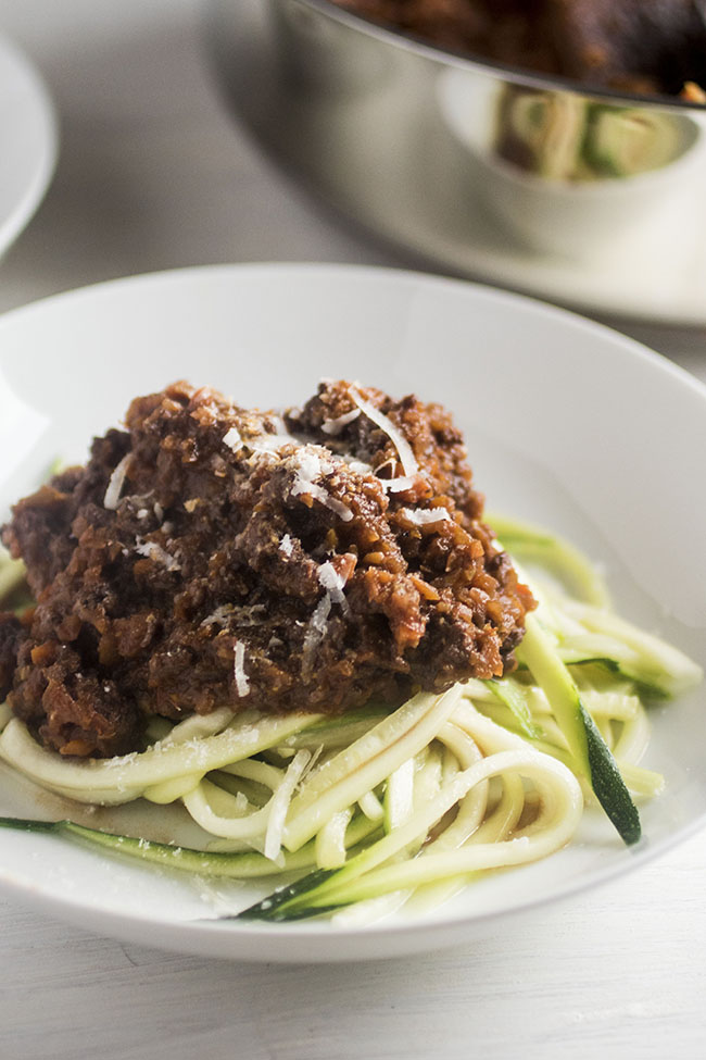white bowl of zucchini noodles topped with bolognese sauce and shredded parmesan