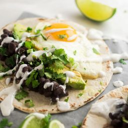 Tortilla filled with fried egg, avocados, and black beans.