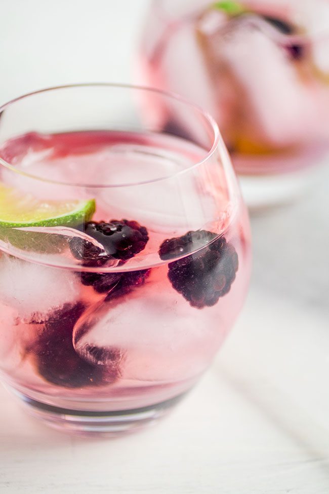 Two cocktail glasses filled with vodka tonics, fresh blackberries, and lime wedges on a white background.