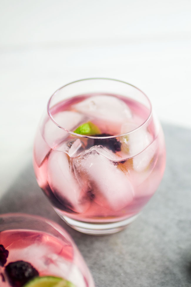 glass cup filled with light pink cocktail and ice cubes on a white background