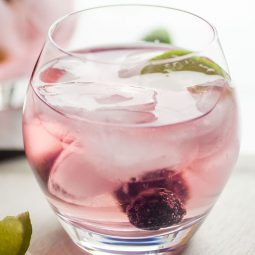 Light pink cocktail in a glass with fresh berries and a lime wedge.
