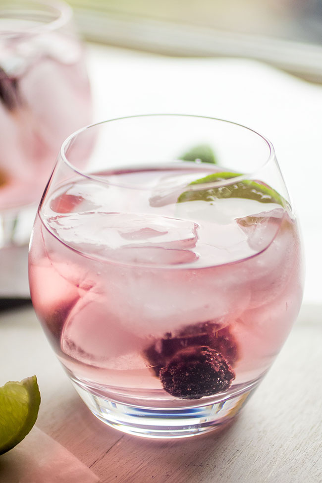 Blackberry vodka tonic garnished with fresh blackberries and a lime wedge.