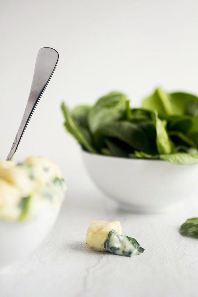 Gnocchi with spinach on a white background with fresh spinach in the background