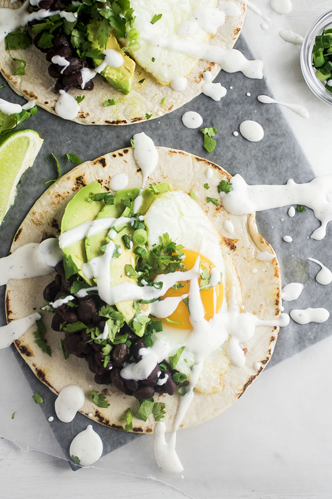 overhead photo of two tortilas topped with fried egg, avocado slices, black beans, and drizzled with lime crema on a white background