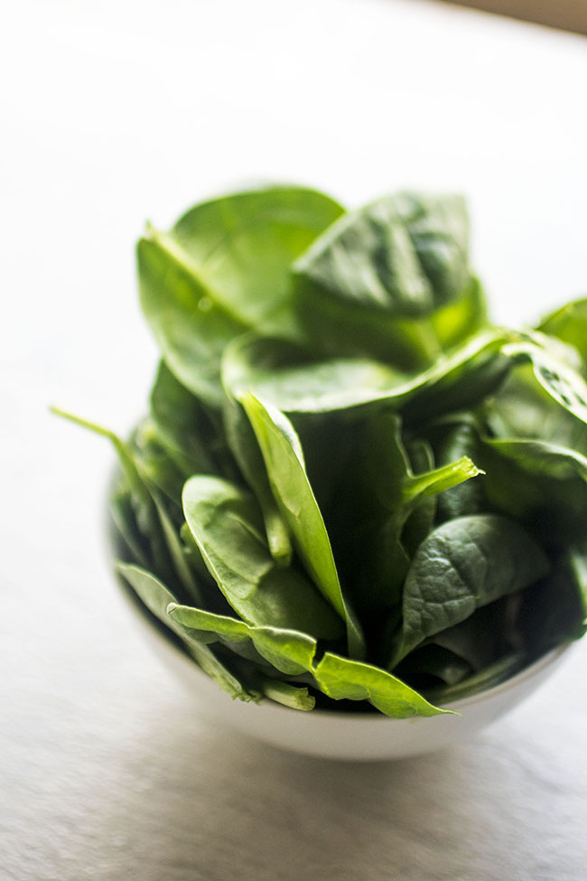 fresh spinach in a white bowl on a white background