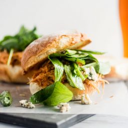 Shredded chicken sandwich with fresh arugula and blue cheese on a white background.