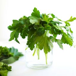 Fresh parsley in a glass jar filled with water.