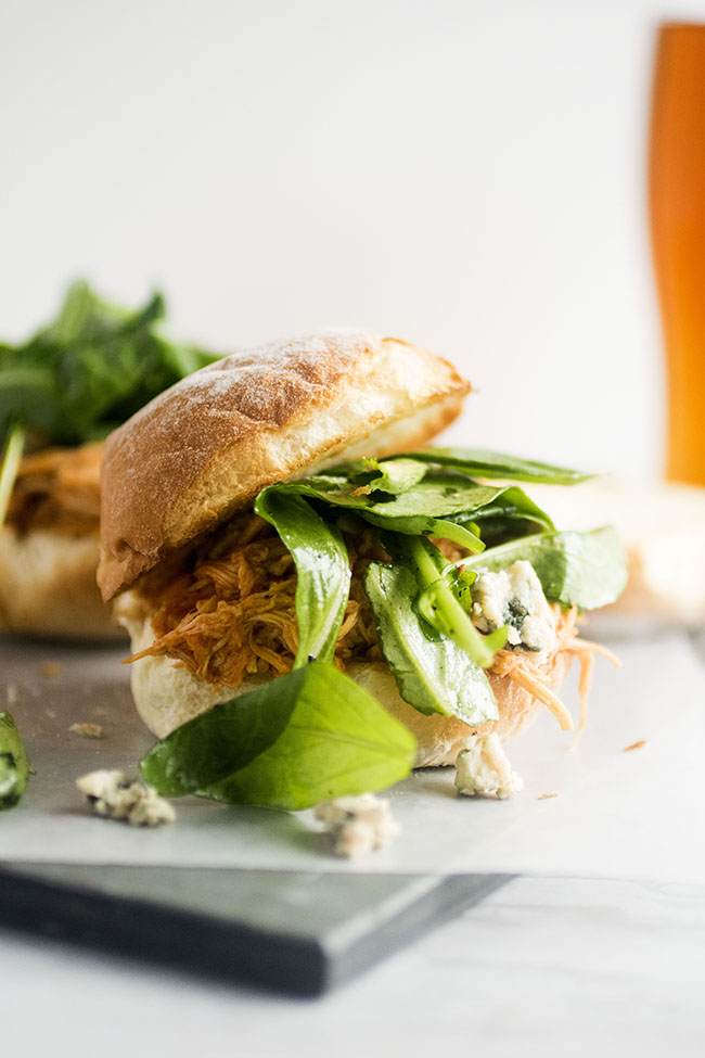 Chicken slider sandwich with arugula on a slate serving platter with a white background