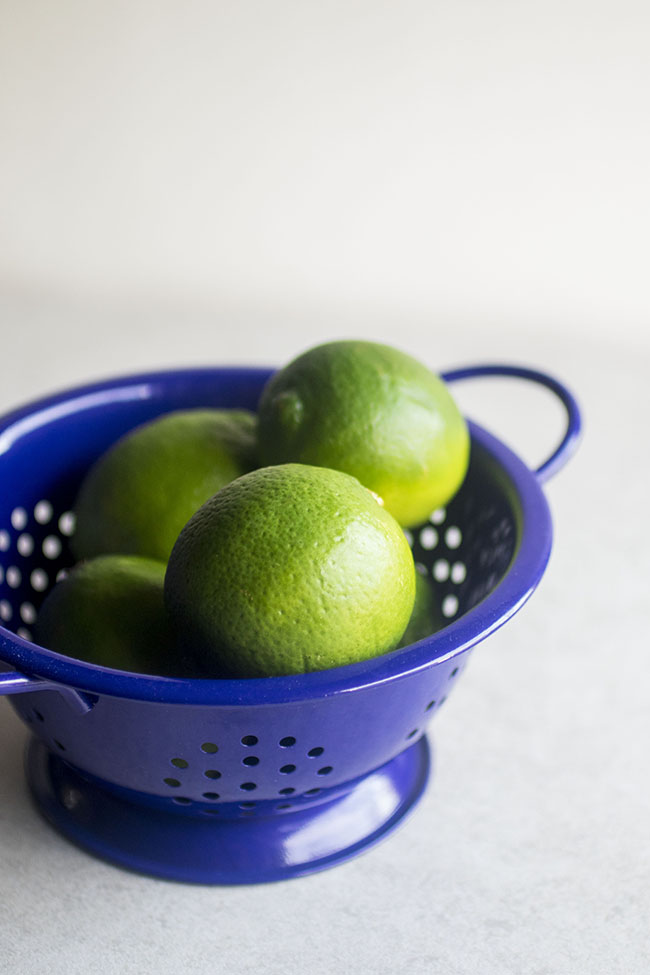 Limes in a bright blue colander.