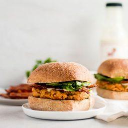 Two salmon burgers on small white plates.