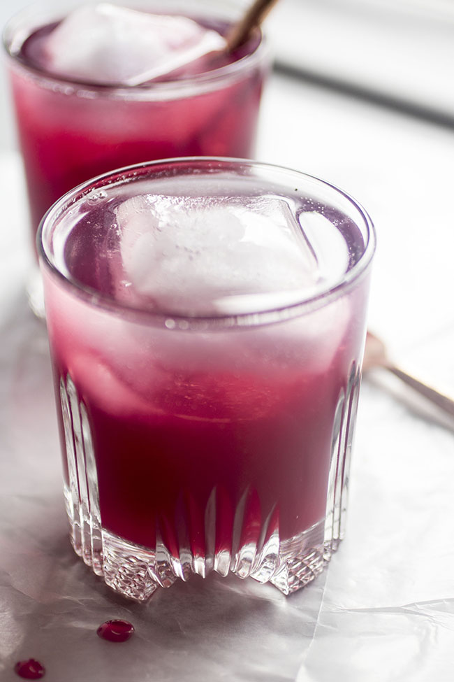 two glass cocktail cups filled with dark pink blueberry cocktails and large ice cubes