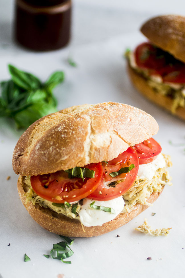 sandwich bun filled with slow cooker chicken, sliced tomatoes, mozzarella and chopped basil on a white background
