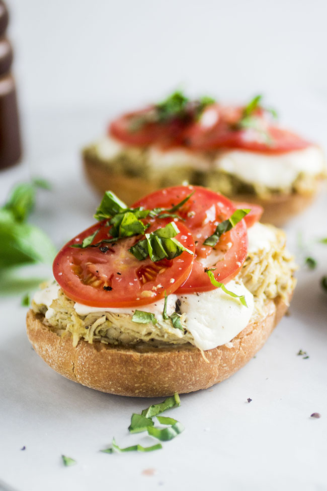 Open faced sandwich with shredded chicken and sliced tomatoes topped with fresh basil on a white background