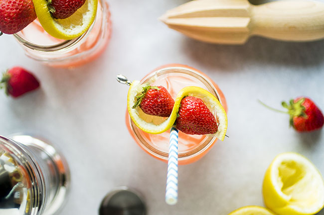 overhead photo of pink cocktail in a mason jar with a blue striped straw garnished with whole strawberries and a lemon slice