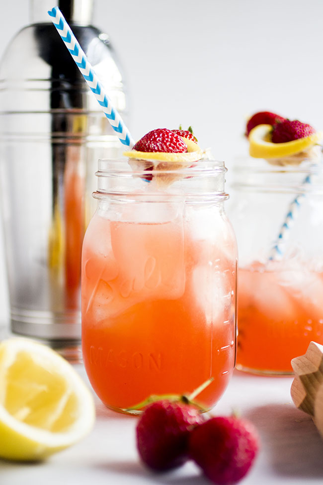 mason jars filled with strawberry whiskey lemonade and a straw with cocktail shaker in background