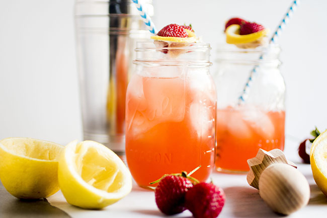 two mason jars filled with strawberry cocktail on a white background surrounded by lemon slices and whole strawberries