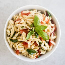 Orzo pasta salad in a small white bowl with a sprig of fresh basil on top.