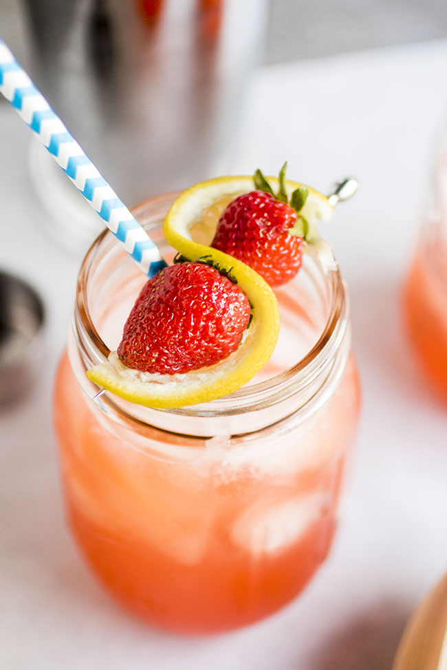 mason jar filled with strawberry whiskey cocktail and a blue straw topped with whole strawberries and lemon slice