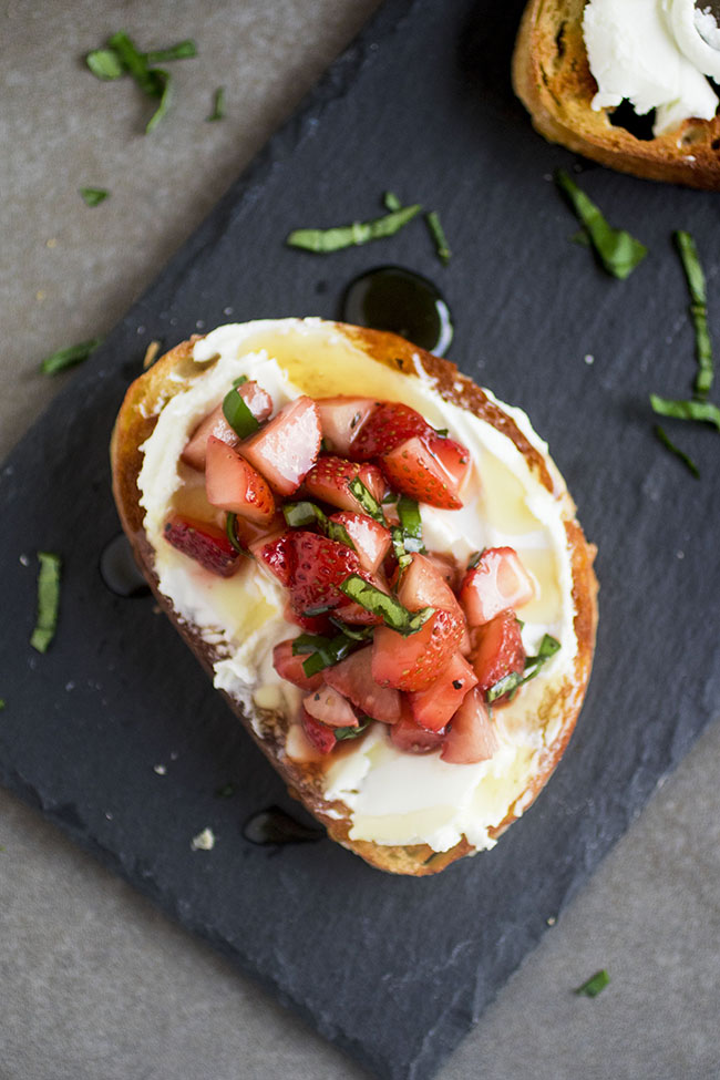 one crostini on a slate platter topped with strawberries surrounded by chopped basil