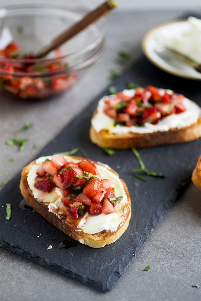 crostini topped with goat cheese and strawberry basil salsa drizzled with honey on a slate platter