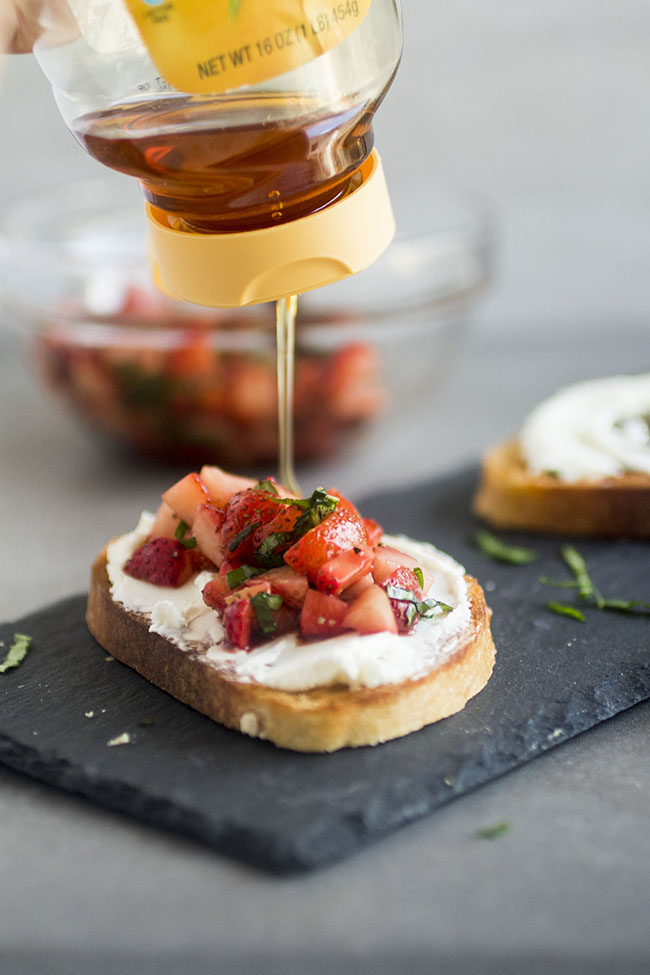 hand drizzling honey over toasted bread topped with goat cheese and strawberries