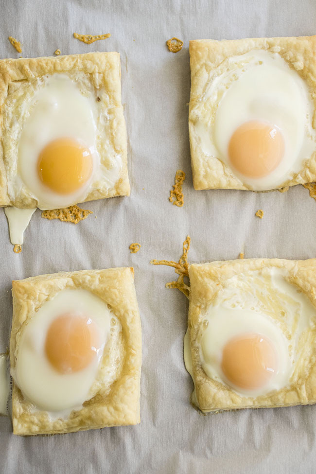 four puff pastry squares with sunny side up eggs on top
