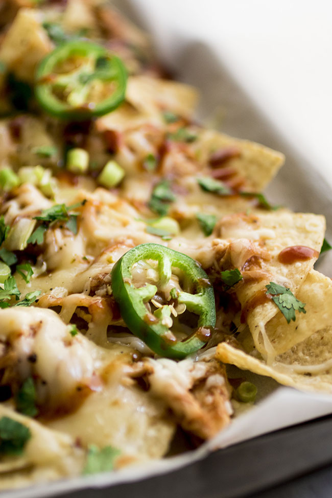 Nachos topped with jalapenos melted shredded cheese cilantro and green onions