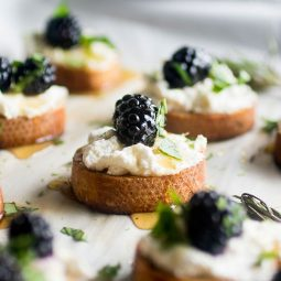 Tray of crostini topped with goat cheese and fresh blackberries.