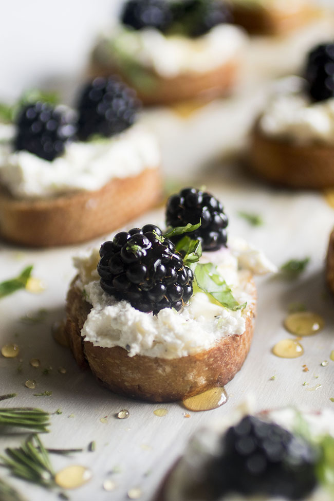Baguette slices topped with goat cheese, blackberries, and basil on a white background.