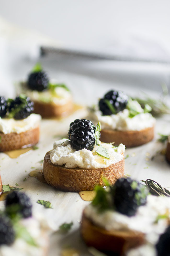 five crostini topped with goat cheese, blackberries, and basil on a white background