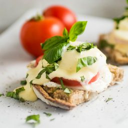 Eggs benedict topped with fresh basil on a white background.