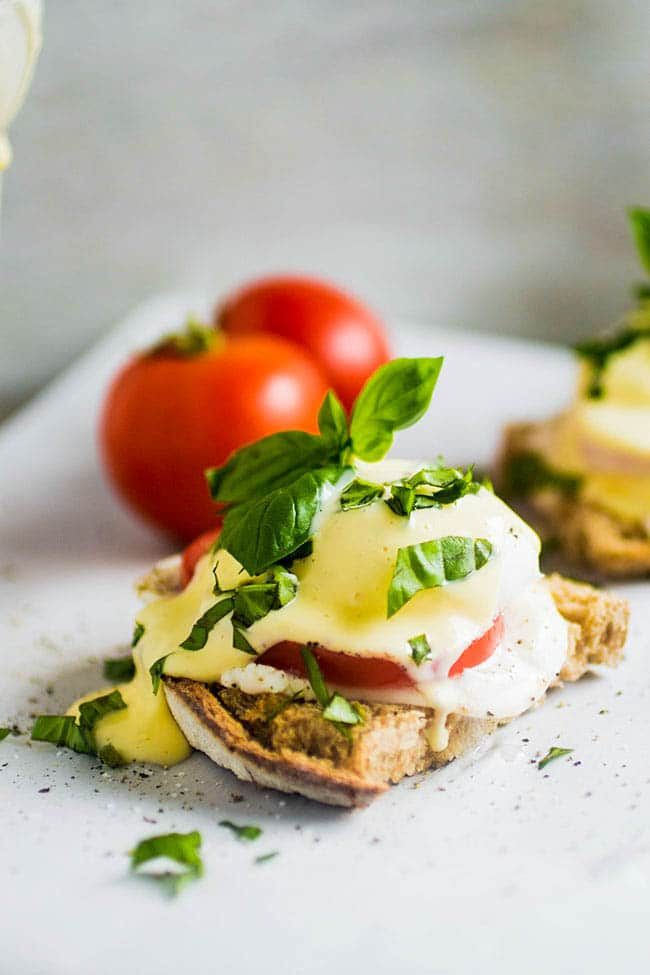 Eggs benedict topped with fresh basil on sourdough toast.