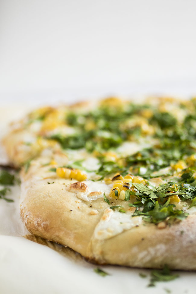 Side photo of white pizza topped with grilled corn and chopped cilantro on a white background