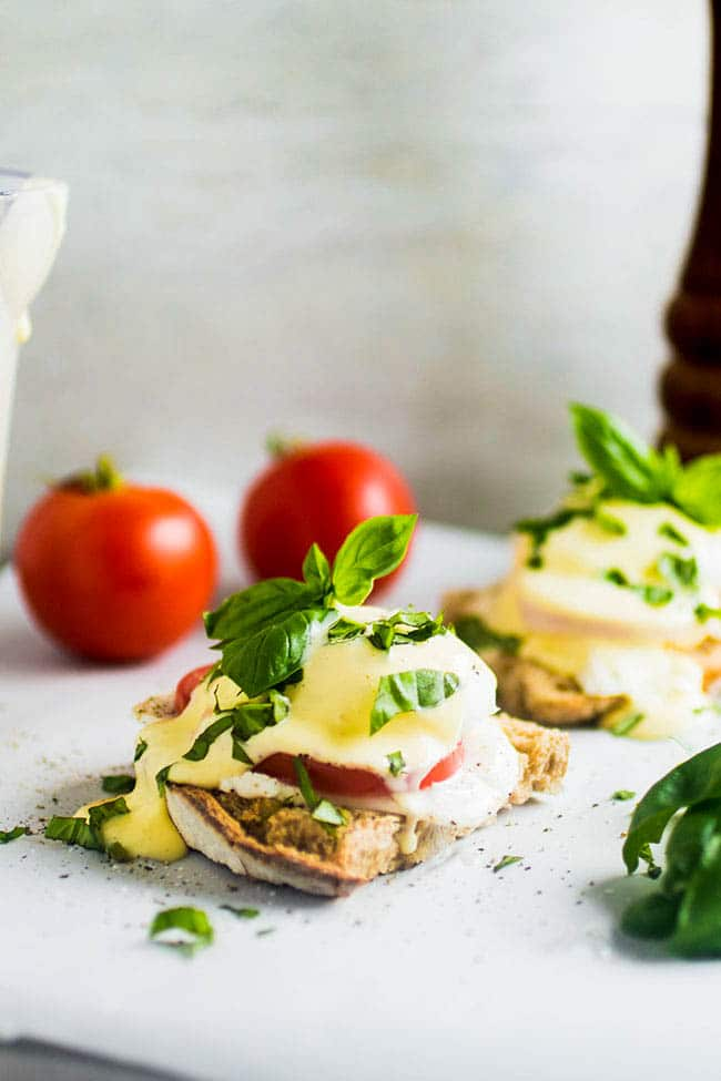 Eggs benedict topped with fresh basil on a white surface with whole tomatoes in the background.