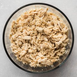 Glass bowl filled with shredded chicken.