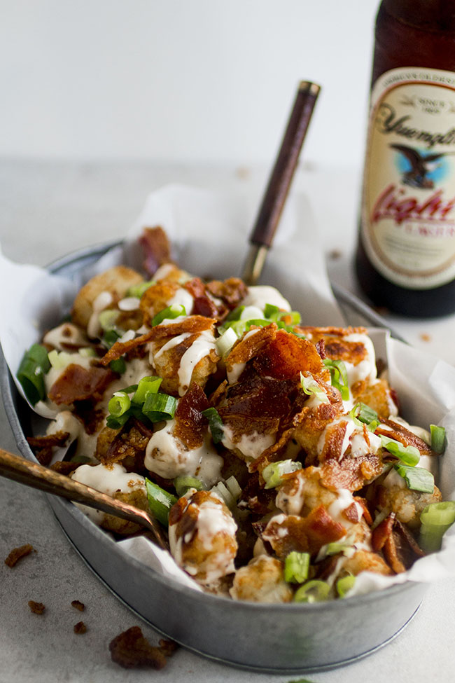 Tater tots topped with cheese sauce, bacon, and green onions in a metal tin with two small forks sticking out and a bottle of beer in the background