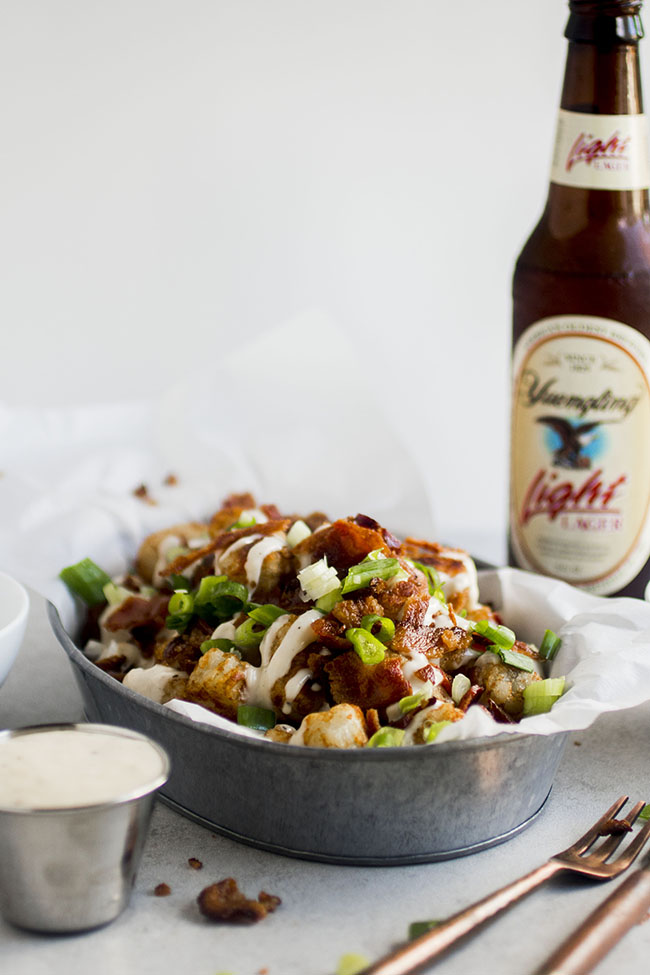 Loaded tater tots in a metal tin lined with parchment paper in front of a beer bottle on a white background and a tin of cheese sauce on the side