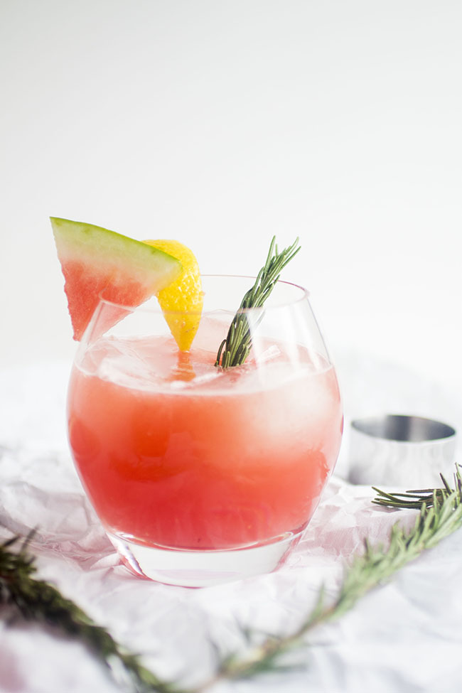 cup filled with rosemary and watermelon cocktail surrounded by sprigs of rosemary and watermelon slices
